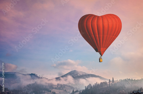 Poster de jardin Montgolfière / Dirigeable Beautiful red air balloon heart shape against blue and pink pastel sky in a sunny bright morning. Foggy mountains in the background. Romantic trip on Valentine's Day. Sport and recreation travel theme