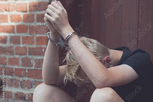 Papel de parede Dejected teenage boy held captive in handcuffs