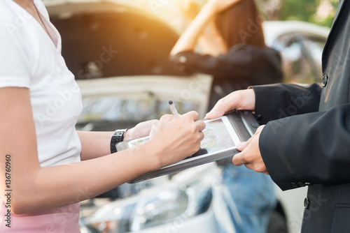 Asian women and insurance agent examining car after accident