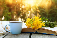 Old Book, Cup Of Coffee Next To Field Flowers