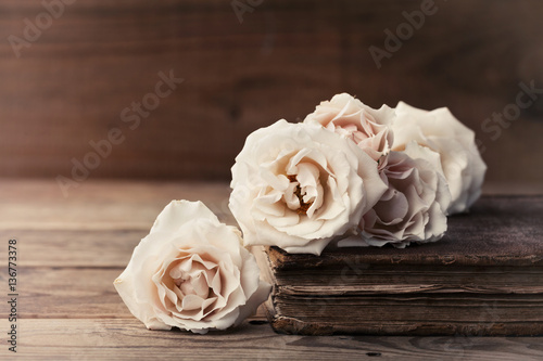 Retro still life with vintage rose flowers and ancient book. Nostalgic composition on old wooden table. - 136773378