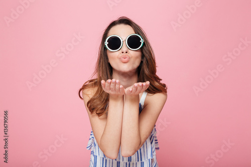 Fotografie, Obraz  Cute young woman in round sunglasses standing and sending kiss