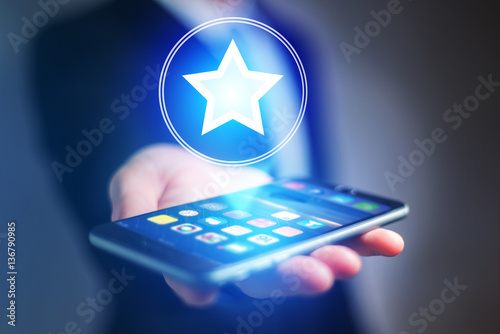 Fotografie, Obraz  Businessman hand holding mobile phone with staricon
