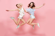 canvas print picture - Two happy joyful young women jumping and laughing together