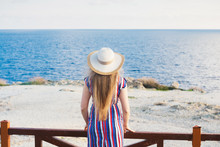 Back View Of Woman Standing In Summer Dress And Hat Looking Out Towards Blue Ocean And Sky