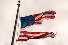 American Flag Torn Down The Middle Waving In The Wind On A Cloudy Sky. Resistance