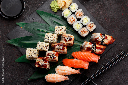 Poster Sushi bar Japanese cuisine. Sushi set on a stone plate and dark concrete background