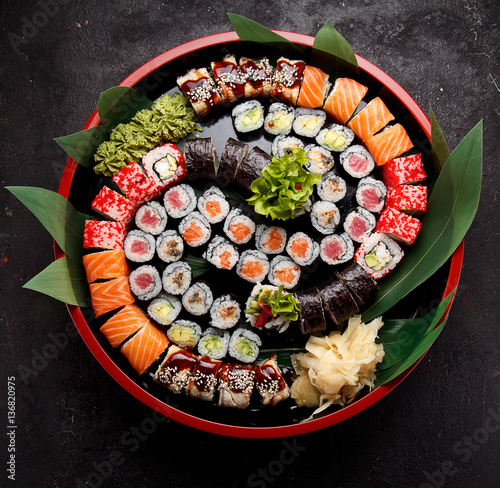 Japanese cuisine. Sushi set on a round wooden plate and dark concrete background.