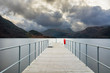 Long pier with British flag pole at Ullswater in the Lake District with moody dramatic clouds.