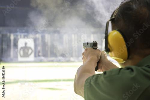 Fotografía  man firing automatic  pistol to target in shooting range