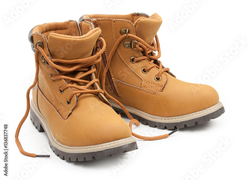 Fotografía  Yellow leather stylish children's shoes, unlaced boots isolated