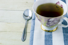 Cup Of Tea With Napkin On Light Wood Background