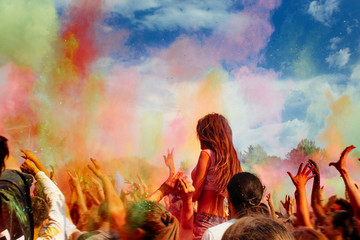 happy people crowd partying under colorful powder cloud at holi