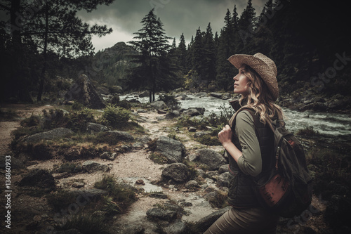 Beautiful woman hiker near wild mountain river. Canvas Print