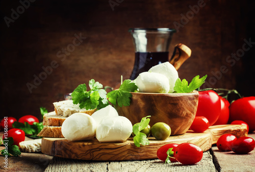 Staande foto Buffel Mozzarella cheese, bread, olives and tomatoes, snack plate. Vint