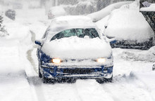 A Snow Covered Car Drives In W...