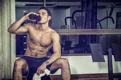 Fotografia  Atrakcyjny sportowy bez koszuli młody człowiek pije proteinowego potrząśnięcie o