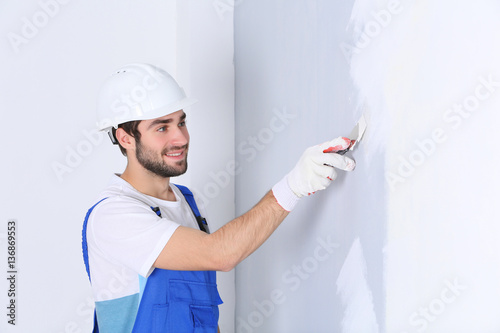 Young worker making repair in room