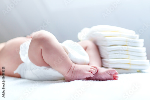 Feet of newborn baby on changing table with diapers