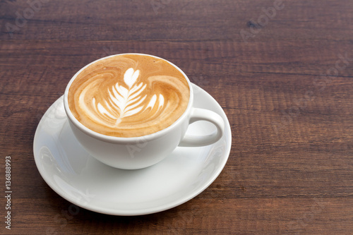Fotografie, Obraz  Coffee cup of rosetta latte art on wooden background with copy s
