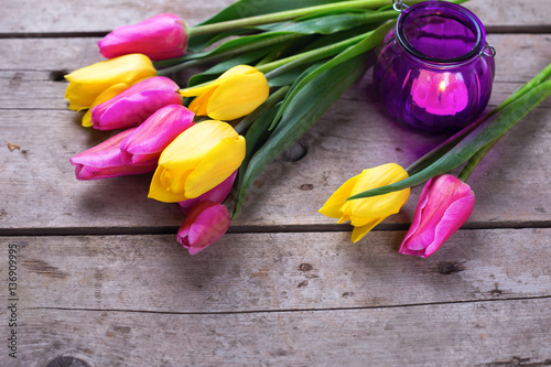 Photo  Bright  spring tulips and  violet candle on vintage wooden backg