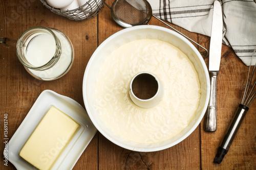 Fotomural Masa para bizcocho y torta con leche, mantequilla sobre mesa de madera rústica
