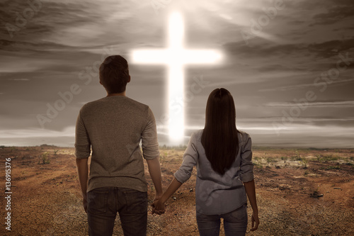 Valokuva  Asian couple holding hand each other looking bright cross shape