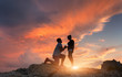 Silhouettes of a man making marriage proposal to his girlfriend on the mountain peak at sunset. Landscape with silhouette of lovers against colorful sky. Couple. People, relationship. Traveling couple