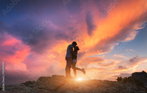 Poster Oranje eclat Silhouettes of a hugging and kissing man and girlfriend on the mountain peak at sunset. Man and woman. Landscape with silhouette of people against colorful sky. Couple, lovers, relationship