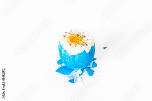 Staande foto Kip Kaputtes Osterei nach Eierpicken vor weißem Hintergrund mit Salz und Pfeffer