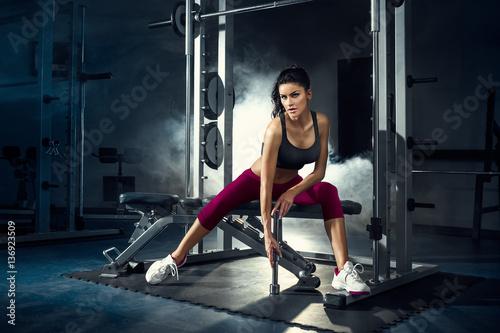 Obraz fitness, siłownia, kobieta, sportowiec - Młoda seksowna dziewczyna trenuje w siłowni z ciężarami - fototapety do salonu