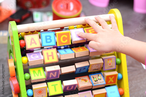 Fotomural  Close up of toddler's hands playing with colorful educational toy