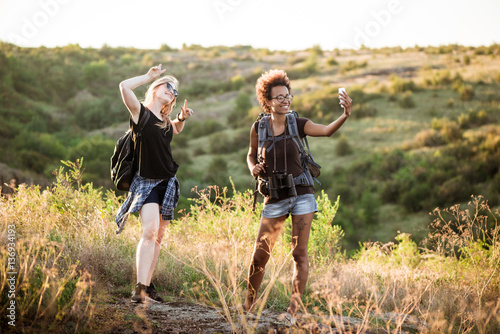 Foto op Canvas Jacht Girls with backpacks smiling, making selfie, traveling in canyon.