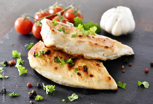 Fotografía  Grilled chicken breast on a slate plate with herbs and cherry tomatoes, garlic and peppercorns