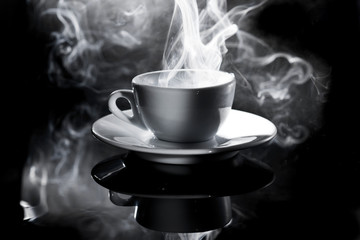 small white cup of steaming coffee on a black background