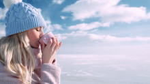 Woman Drinking A Hot Drink In Winter Outdoors