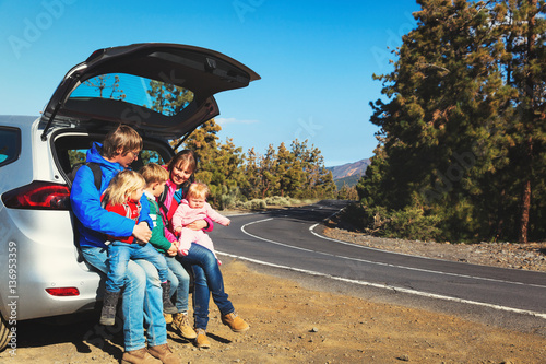 Fototapeta  happy family with tree kids travel by car on road