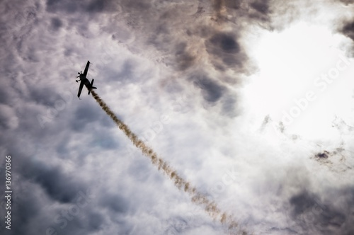 Silhouette of an airplane with smoke; Wallpaper Mural
