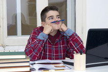 Child Distracted Thinking On The Desk Of The School Or Home