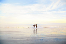 Couple Standing On Wet Sand On Beach And Looking Away. Man And Woman Relaxing On The Sea Ocean On Sunset. Back View. Peaceful Scene, Calming Waves, Pastel Cloudy Sky, East Coast. Happy Time Together.