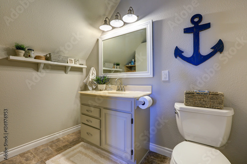 Fotografie, Obraz  Marine style powder room interior in soft tones features vaulted ceiling over creamy white single bathroom vanity and toilet
