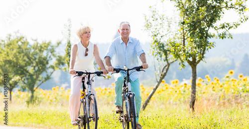 Fotobehang Zwavel geel Senioren, Paar aus Frau und Mann, fährt Fahrrad an einem Sonnenblumen Feld