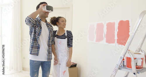 Couple uses virtual reality glasses to choose paint color for room while standin Canvas-taulu