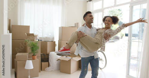 Valokuva  Ecstatic young couple celebrating their new home with the young man holding his