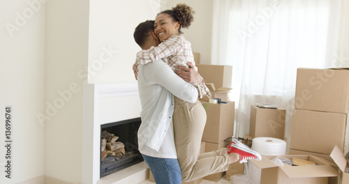 Valokuva  Joyful young couple celebrating their move to a new home hugging and laughing in