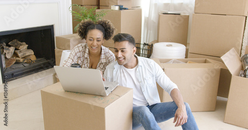 Valokuvatapetti Happy mixed race couple sitting on the floor among unpacked carton boxes and using laptop computer to plan the future in their new apartment they just moved in
