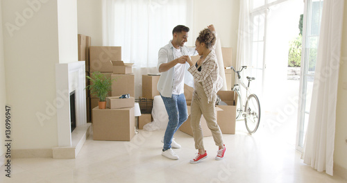 Happy young couple celebrating moving home dancing together in the living room s Canvas-taulu