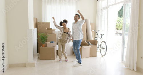 Young couple dancing for joy in the living room of their new home with packing b Canvas-taulu