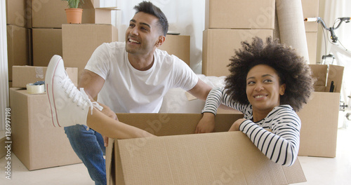 Smiling young woman in a cardboard carton with her grinning alongside as they admire the living room of their new home against a backdrop of stacked packed cartons Canvas-taulu