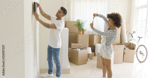 Fotografía  Young couple hanging pictures in their new home aligning it on the wall together